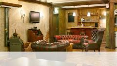 De zitkamer van Klein Plezier heeft een gezellige huisbar en een grote serre met uitzicht op de tuin.